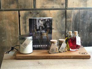 Houten plank met receptenboek en potjes olie, azijn en kruiden.